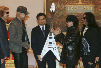 Thailand's Prime Minister Abhisit Vejjajiva holds a guitar presented to him by members of Scorpions in Bangkok