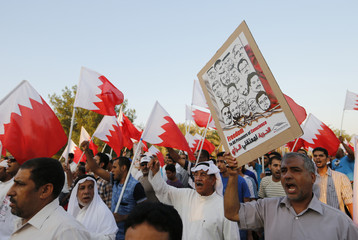 A protester holds a picture of political detainees while demanding for their release, during an anti-government protest in Budaiya, west of Manama