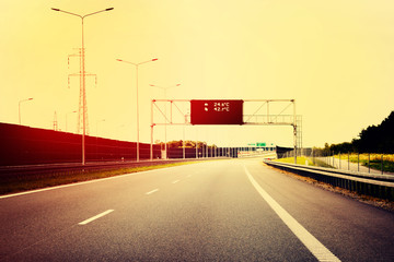 A Highway With Traffic on a Bright And Sunny Day. The Digital Temperature Indicator Shows the High Temperature on the Road (Filtered image processed vintage effect).