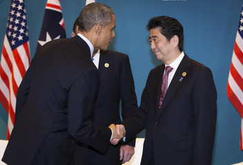U.S. President Barack Obama shakes hands with Japan's Prime Minister Shinzo Abe during a tri-lateral meeting with Australian Prime Minister Tony Abbott at the G20 conference in Brisbane