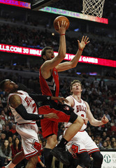 Toronto Raptors' Bargnani goes to the basket against Chicago Bulls' Watson  and Asik during their NBA basketball game in Chicago