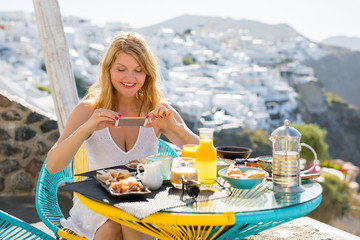 Woman taking photo of her breakfast with mobile phone