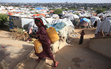 An internally displaced Somali girl carries a jerry-can of water as she walks through their makeshift shelters at Sayyidka camp in the Howlwadag district