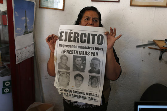Maria Orozco, mother of a man who was abducted, shows a poster in Iguala