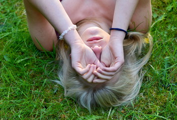 girl's hands lying in the grass..