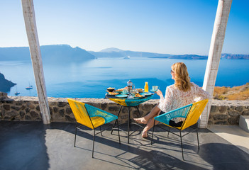 Woman enjoying breakfast with beautiful view from terrace