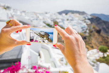 Tourist taking picture of Santorini with mobile phone