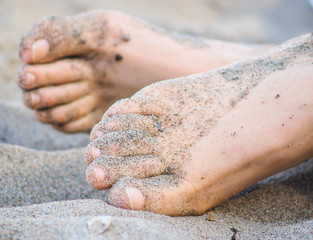 Feet of one unrecognizable caucasian person resting in sand, with wet sand on feet