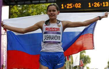 Russia's Elena Lashmanova holds her national flag as she celebrates after winning the women's 20km race walk final at the London 2012 Olympic Games at The Mall