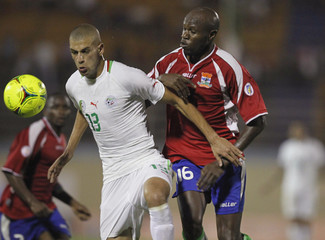 Algeria's Slimani fights for the ball with Gambia's Abdou during their African Nations Cup qualifying soccer match at Tacheker stadium in Blida