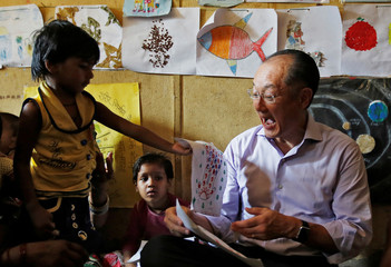 World Bank President Jim Yong Kim reacts as a girl shows him a drawing, during his visit to an Integrated Child Development Services (ICDS) centre in New Delhi