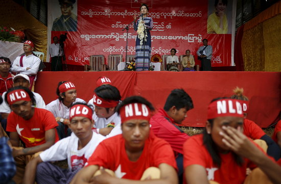 Security men sit as Myanmar pro-democracy leader Aung San Suu Kyi gives a speech on voter education at the Hopong township in Shan state