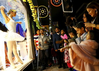 People watch a ballerina dance in a shop window during Diwali celebrations in Leicester