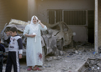 A wounded woman makes a phone call at her damaged house after a bomb attack in central Baghdad