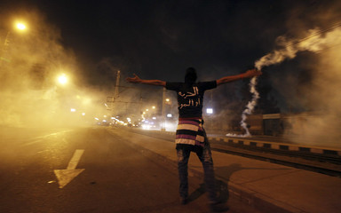 A protester, who opposes Egyptian President Mohamed Mursi, shouts slogans amidst teargas released by riot police during clashes in front of the presidential palace in Cairo