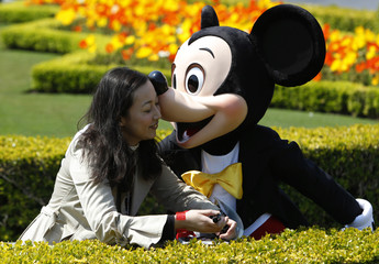 A visitor is kissed by Disney character Mickey Mouse at Tokyo Disneyland in Urayasu