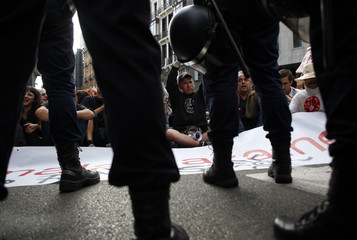 Police stand guard as demonstrators sit on the street in front of Spain's parliament in Madrid