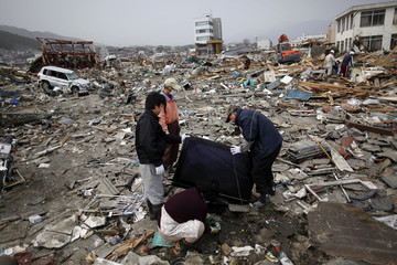 People retrieve belongings from the ruins of their home in the destroyed residential part of Ofunato