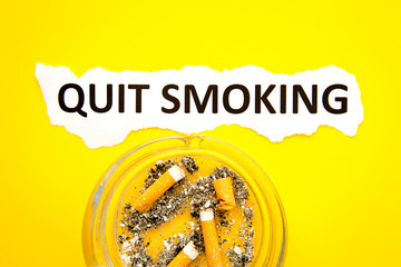Quit Smoking - Health - with ashtray and printed text on yellow background