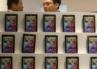 People walk past a wall displaying mockup HTC mobile phones at a shopping mall in Taipei