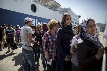 Abeer (R), a 26-year-old Syrian migrant from Deir Al Zour in war-torn Syria, queues with others to buy a ticket to embark a ferry to Athens on the Greek island of Lesbos
