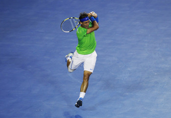 Nadal of Spain follows through on a return to Novak Djokovic of Serbia during their men's singles final match at the Australian Open tennis tournament in Melbourne
