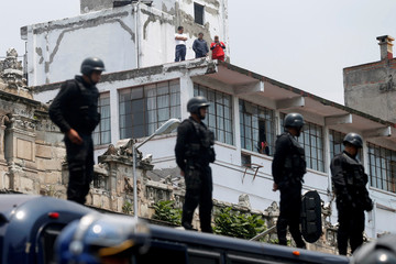 Riot police keep watch over protesters from National Coordination of Education Workers (CNTE) teachers union as they take part in a march against President Pena Nieto's education reform in Mexico City