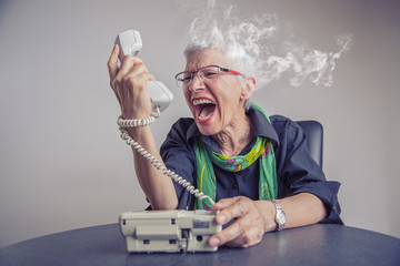 Angry, enraged senior woman yelling at a landline office phone, unhappy with customer service provided by the agent on the other side, giving off steam and smoke