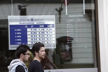 People walk past a bank office with deposit rates and currency exchange rates displayed in Vilnius