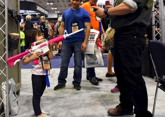 A young girl, who is already an NRA lifetime member, gets her photo made holding a rifle painted pink and white in the trade booths during the NRA's annual meeting in Nashville