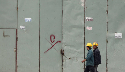 Workers go for lunch outside a construction site in Hanoi
