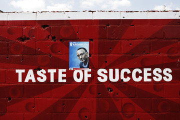 A poster for Rwandan President Paul Kagame is pasted over a mural advertising beer in the capital Kigali
