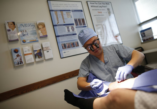 Doctor Chiou debrides a leg wound on patient Larry Kirk in Peoria