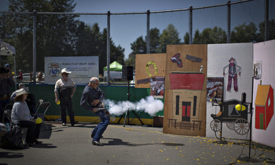 Nielson of Loveland, Colorado, draws and fires his gun at a balloon target during the Canadian Open Fast Draw Championships in Aldergrove