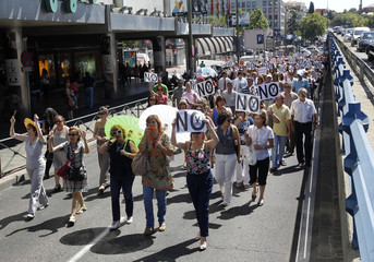 Civil servants hold up placards and block the street as they protest against government austerity measures in Madrid