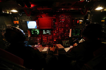 Captains Fleming Thompson and Rylan Kabanuck work on the navigation desk of a U.S. Air Force B-52 during a training mission in the United Kingdom's airspace