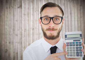 Man with calculator against blurry wood panel