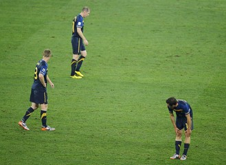 Australia's Moore reacts with his team mates after Germany's third goal was scored during the 2010 World Cup Group D soccer match against Australia at Moses Mabhida stadium in Durban