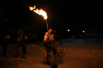 """A man dressed in a costume made of animal fur, called """"kuker"""", carries a torch during a festival in the town of Batanovtsi"""