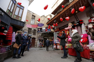 People pose for a picture along a street decorated for Valentine's Day in al-Qaimaryeh street, in old Damascus