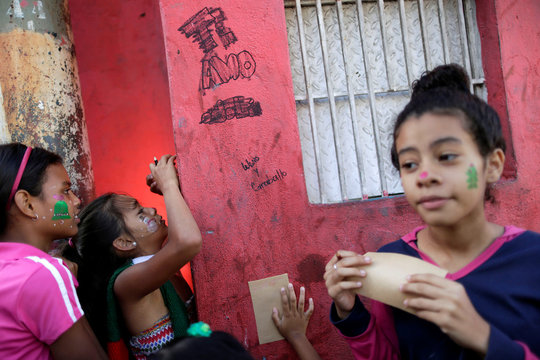 Children write letters during a visit by Santa Claus to residents of the slum of Petare in Caracas