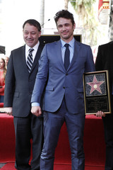 Actor James Franco stands atop his newly unveiled star on the Hollywood Walk of Fame with friend and director Sam Raimi in Hollywood