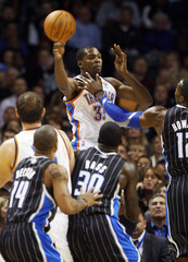 Oklahoma City Thunder forward Kevin Durant looks to pass over Orlando Magic defenders during an NBA game in Oklahoma City.