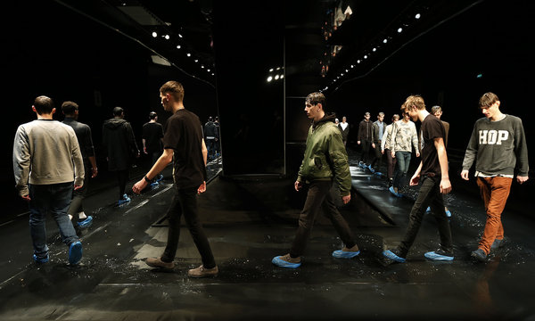 """Models wear protective shoe covers on the catwalk during rehearsal before Topman Design Autumn/Winter 2014 collection presentation during """"London Collections: Men"""" in London"""
