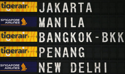 Tiger Airways and Singapore Airlines logos are displayed on a board showing flight details at Changi Airport in Singapore