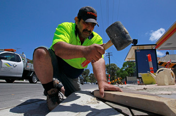 A construction worker uses his hammer on a pedestrian path in Sydney
