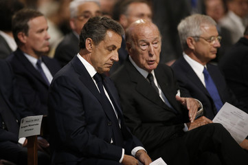 Nicolas Sarkozy, head of France's Les Republicains political party and former French president, speaks with former French President Valery Giscard d'Estaing before a mass at the Notre-Dame Cathedral in Paris