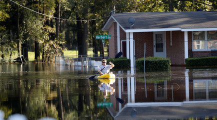 Parker Uzzell checks on his property with a kayak along Herbert Street after the effects from Hurricane Matthew in Goldsboro