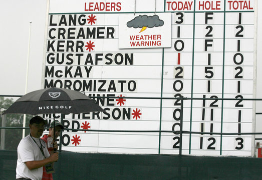 Spectators walk past a scoreboard after play was suspended for rain and lightning during the second round of the Women's U.S. Open Golf Championship in Oakmont