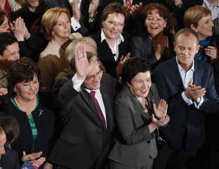 Polish Prime Minister Tusk applauds as Komorowski, speaker of the Parliament and presidential candidate from Civic Platform (PO) waves next to his wife Anna at his Party election headquarters in Warsaw